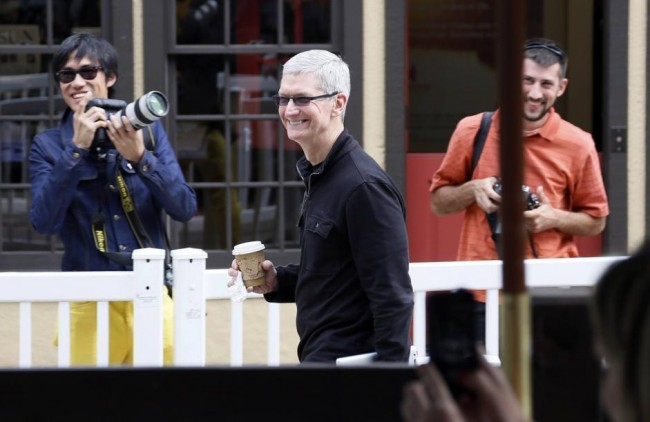 Tim Cook, Apple CEO smiles as he looks at a news conference being held by Eric Schmidt, executive chairman of Google at the annual Allen and Co. conference in Sun Valley